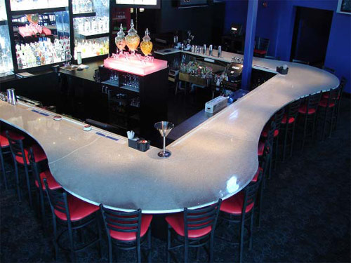 UV Countertops on a bar top that is surround by red chairs.