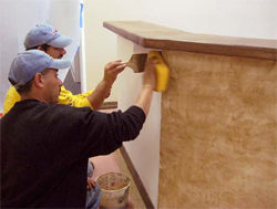 Workers apply Adobe Mirastain II to accent the sides of the front counter.