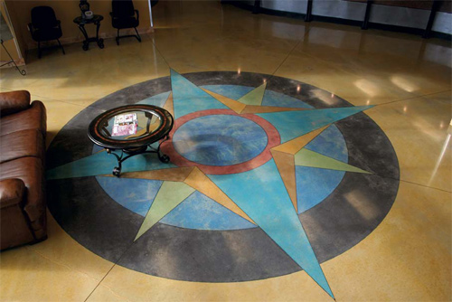 A colorful compass that has been stained into a concrete floor.