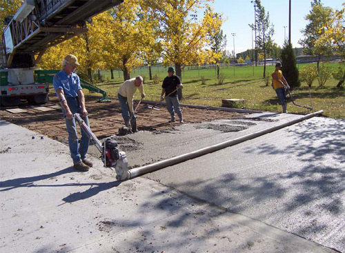 roller screed is a pipe suspended over a wet concrete surface. A motor spins the pipe in the direction opposite to which it is pulled. Photo courtesy of Lura Enterprises Inc.