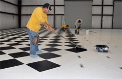 Concrete by Hallack employees diligently working on applying to color to this concrete garage.