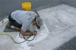 Josh Cornwall, a 2003 Concrete Industry Management graduate, works on a decorative concrete project on the Middle Tennesee State University campus in fall 2009. He is etching the pattern of the MTSU logo, which was later stained. The project was a collaboration between members of the ASCC Decorative Concrete Council and the MTSU CIM Program.
