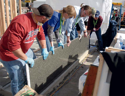 PreiTech Corp. owner and project instructor Mike Eastergard helps CIM students construct a Sept. 11 memorial at 2010 World of Concrete.