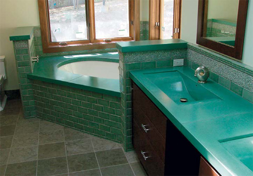 Teal colored bathroom concrete countertop and bath surround.
