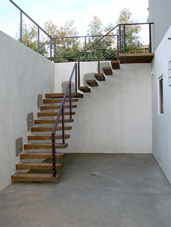 Stairs lead out of this simple and clean outdoor patio to an upper deck.