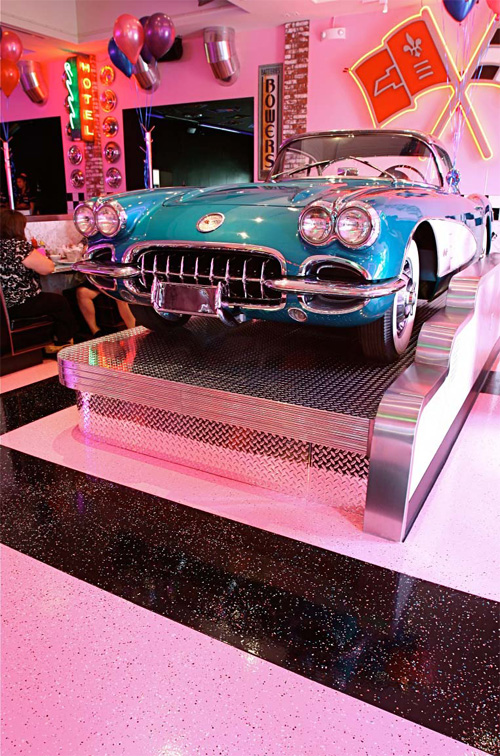 Old corvette sits on a chrome stand in a 50s style diner