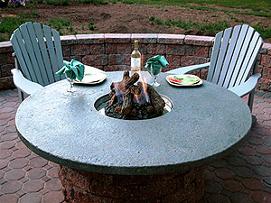 Adirondack chairs around a green circular concrete fire pit.