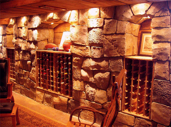 Concrete wine cellar that is lit and staged to have a very cozy look.
