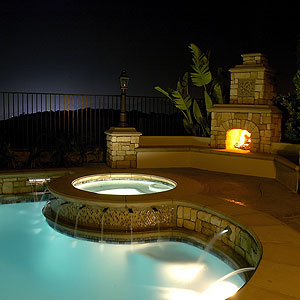 A look at a pooldeck that is light up at night with a large outdoor fireplaces in the background.