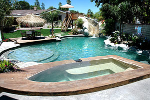High end pool with hot tub surrounded by colored concrete.