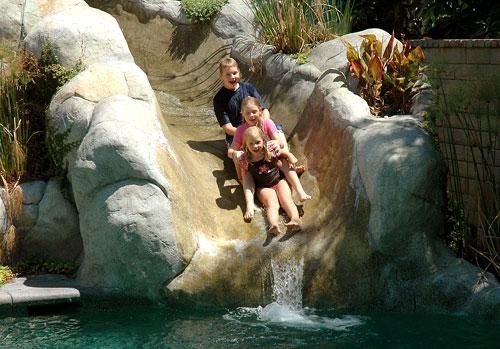 Kids sliding down a concrete waterslide.