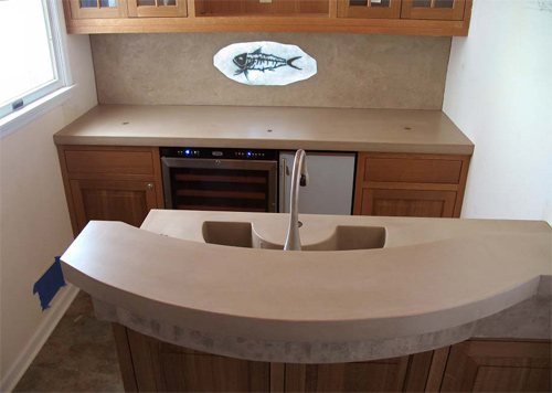 Concrete panels are great for backsplashes as they offer seamless, easy-to-clean areas. Here, a plasma-cut steel fish skeleton is set in translucent concrete. The backsplash panel has a split-face limestone texture that is suggestive of the rock that would host the skeleton naturally.