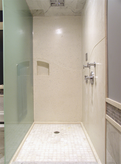 "In this ""shower niche,"" J&M Lifestyles LLC carried a ""wave"" theme in the sink and tub over to the seams in the shower panels to make the seams look purposeful, rather than necessary."