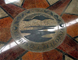 The Swansons incorporated the city seal of Redding into their design for the floor of The Atrium Building after noticing the logo on a manhole cover. Colledi Signs used a photo of the manhole to fashion a set of vinyl sandblasting stencils.