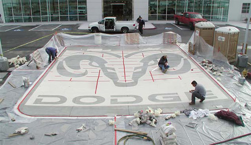 After the stencil has been adhered, computer-rendered precut material was removed, revealing the final design of the Dodge logo. Panel seams and exposed edges are being covered for sandblasting, which will expose black glass aggregate in the gray concrete.