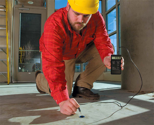 A man in a red shirt and a yellow hard hat test the concrete with a moisture meter.